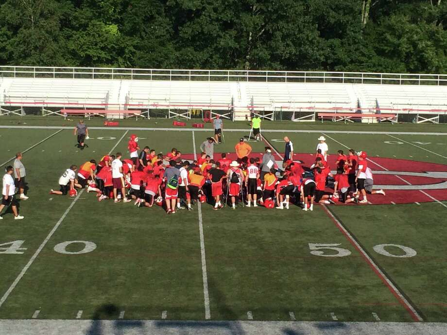 The New Canaan football team gathers with its coaches after a preseason afternoon practice on Tuesday, Aug. 26. Photo: Andrew Callahan / New Canaan News