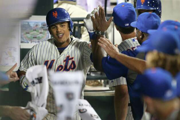 New York Mets' Juan Lagares celebrates in the dugout after hitting a two-run home run in the fourth inning of a baseball game against the Atlanta Braves on Tuesday, Aug. 26, 2014, in New York. (AP Photo/John Minchillo) ORG XMIT: NYM116 Photo: John Minchillo / FR170537 AP