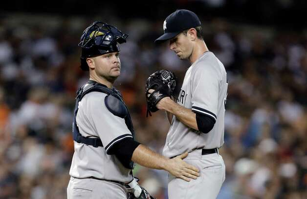 New York Yankees catcher Brian McCann, left, talks with pitcher Brandon McCarthy after walking Detroit Tigers' Rajai Davis with the bases loaded to score J.D. Martinez in the second inning of a baseball game in Detroit Tuesday, Aug. 26, 2014. (AP Photo/Paul Sancya) ORG XMIT: MIPS105 Photo: Paul Sancya / AP
