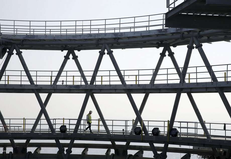A man walks on one of the communication rings on the top of One World Trade in New York, Tuesday, Aug. 26, 2014.  (AP Photo/Seth Wenig) Photo: Seth Wenig, Associated Press