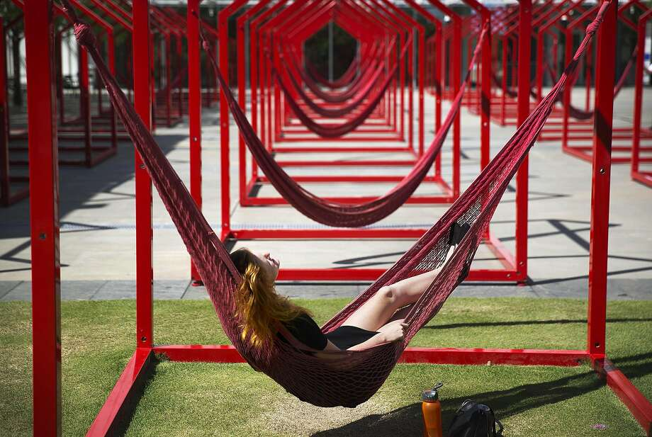 Katie Ledbetter, of Pensacola, Fla., sits in a hammock at the Mi Casa, Your Casa art installation at the High Museum, Tuesday, Aug. 26, 2014, in Atlanta. The installation is comprised of more than 35 three-dimensional open house frames serving as a blank canvas which features hammocks, easels, bins of chalk, and buckets of bubble water to encourage visitors to engage with these environments. (AP Photo/David Goldman) Photo: David Goldman, Associated Press