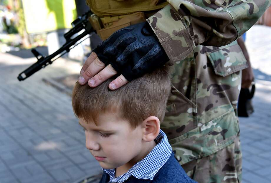 """TOPSHOTS A Sich special volonteer battalion member touches his child on August 26, 2014 during an oath-taking and farewell ceremony in Kiev. The battalion is leaving the Ukrainian capital to take part in anti-terrorists operation (ATO) in the east of the country. Kiev's security services on August 26 released a video purporting to show captured 10 Russian soldiers captured on its territory who a Moscow military source claimed had crossed into Ukraine """"by accident.""""  AFP PHOTO / SERGEI SUPINSKYSERGEI SUPINSKY/AFP/Getty Images Photo: Sergei Supinsky, AFP/Getty Images"""