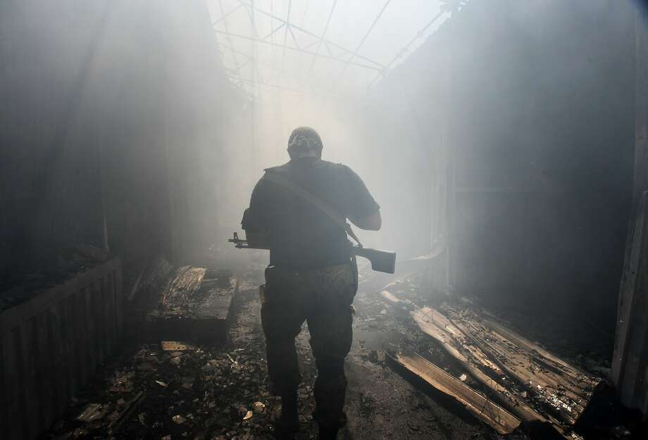 A Pro-Russian rebel walks in a passage at the local market damaged by shelling in Petrovskiy district in the town of Donetsk, eastern Ukraine, Tuesday, Aug. 26, 2014. On Tuesday several shells hit the local market and nearby houses during the mortar duel between Pro-Russian rebels and Ukrainian army. (AP Photo/Mstislav Chernov) Photo: Mstislav Chernov, Associated Press