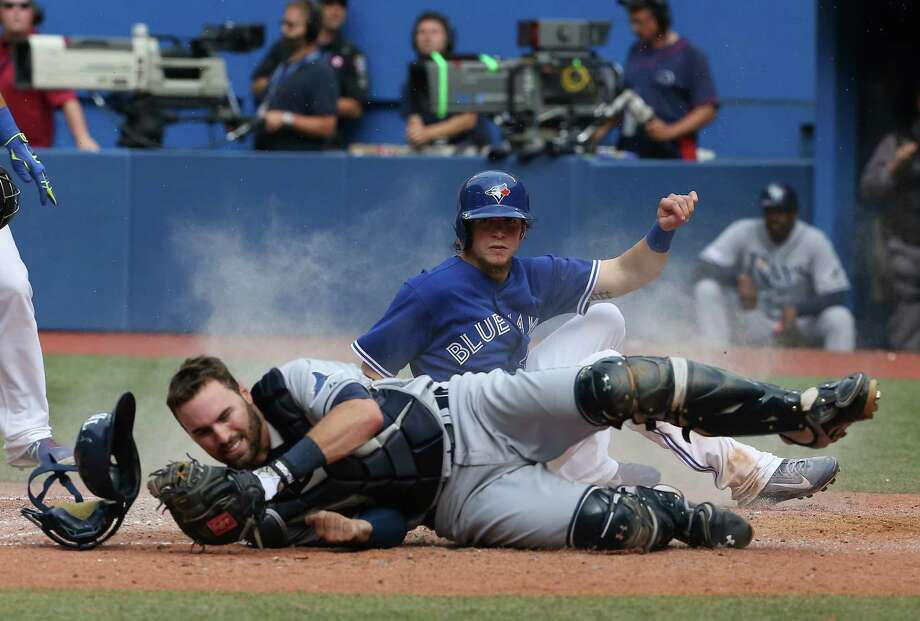 New Canaan native and former Rays catcher Curt Casali cannot hold onto the ball, as the Blue Jays' Colby Rasmus, 28,  slides safely across home plate to score the winning run in the 10th inning of a MLB game on August 23, at the Rogers Centre in Toronto, Ontario, Canada. Photo: Tom Szczerbowski, Getty Images / 2014 Getty Images