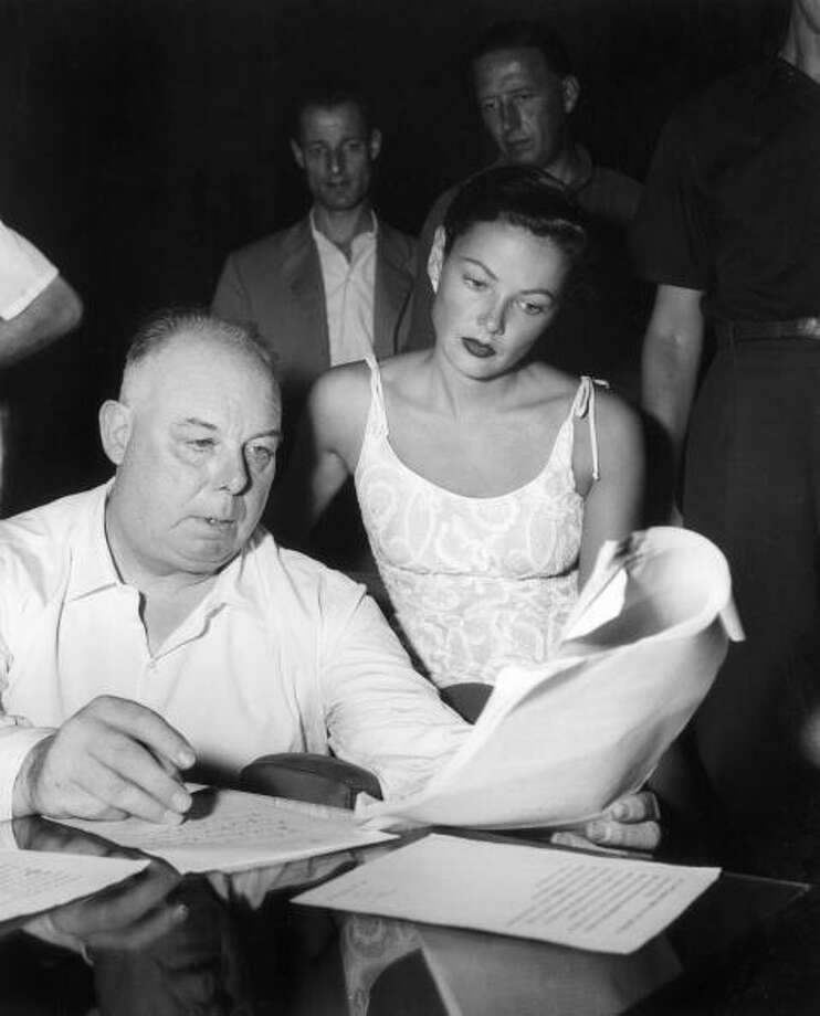 American actor Gene Tierney (1920 - 1991), wearing a lace top, sits next to French director Jean Renoir (1894 - 1979), as they look over the preview of the program for the annual Venice Film Festival, Italy.  (Photo by Hulton Archive/Getty Images) Photo: Hulton Archive, Getty Images