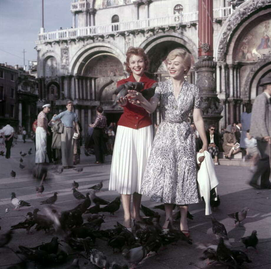 French actress Francoise Arnoul  and Italian actress Giulietta Masina posing among the pigeons in San Marco square during the 16th Venice International Film Festival. Venice, September 1955 (Photo by Mario De Biasi/Carlo BavagnoliMondadori Portfolio by Getty Images) Photo: Mondadori, Mondadori Via Getty Images / Mario De Biasi per Mondadori Portfolio