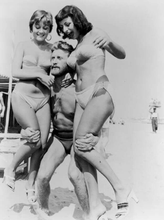 1953:  American actor Kirk Douglas, wearing a swimsuit, lifts two women wearing bikinis on a beach during the Venice Film Festival, Italy.  (Photo by Hulton Archive/Getty Images) Photo: Hulton Archive, Getty Images