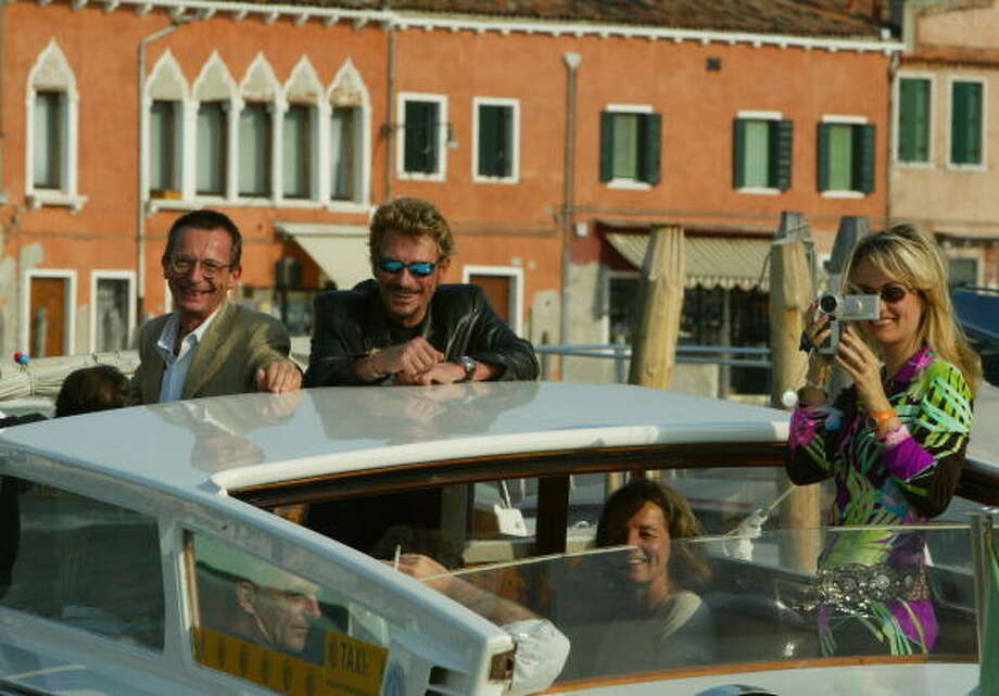 """Director Patrice Leconte, French actor and music star Johnny Hallyday and his wife Laeticia arrive at the Lido during the 59th Venice Film Festival September 2, 2002 in Venice, Italy. Hallyday is in Venice to present the Todd Haynes's film """"L'homme Du Train"""" which is in competition at the festival. The annual Venice Film Festival is one of the oldest and most prestigious cinema events in Europe. The ten day event traditionally sponsors non-Hollywood films and awards the Golden Lion as its top prize.  (Photo by Pascal Le Segretain/Getty Images) Photo: Pascal Le Segretain, Getty Images / 2002 Getty Images"""