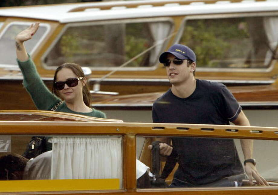 """Actress Christina Ricci (R) waves to photographers as she arrives at Venice Lido with actor Jason Biggs 26 August 2003. Ricci and Biggs are in Venice to present the Woody Allen's out of competition movie """" Anything Else """" to open the 60th international Venice Film Festival on 27 August. Photo: VINCENZO PINTO, AFP/Getty Images"""
