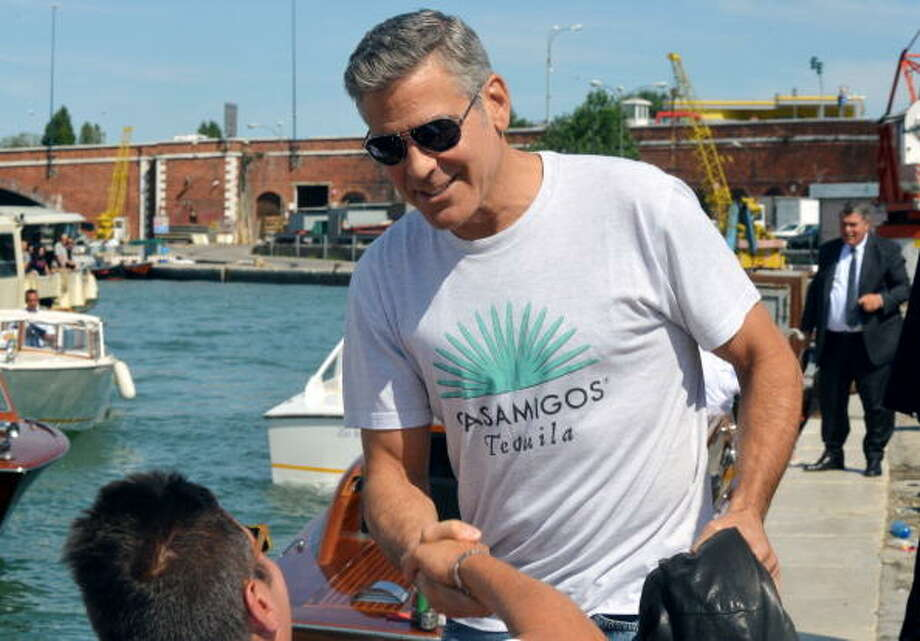 "He's back again:   George Clooney shakes hand with a fan from aboard of a taxi boat in the Venice canal grande upon his arrival on August 27, 2013. Clooney was in Venice to present the movie "" Gravity."" Photo: AFP, AFP/Getty Images"