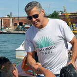 "He's back again:   George Clooney shakes hand with a fan from aboard of a taxi boat in the Venice canal grande upon his arrival on August 27, 2013. Clooney was in Venice to present the movie "" Gravity."""