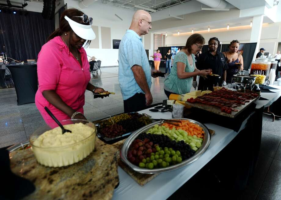 Cheryl Dean, left, and others peruse the free buffet Thursday afternoon. The Jazz at the Lake concert series kicked off at the Event Centre Thursday night with Dean James and his band. There was also free food, beer tastings, and a cash bar for attendees of the free event. Photo taken Tuesday 7/29/14 Jake Daniels/@JakeD_in_SETX