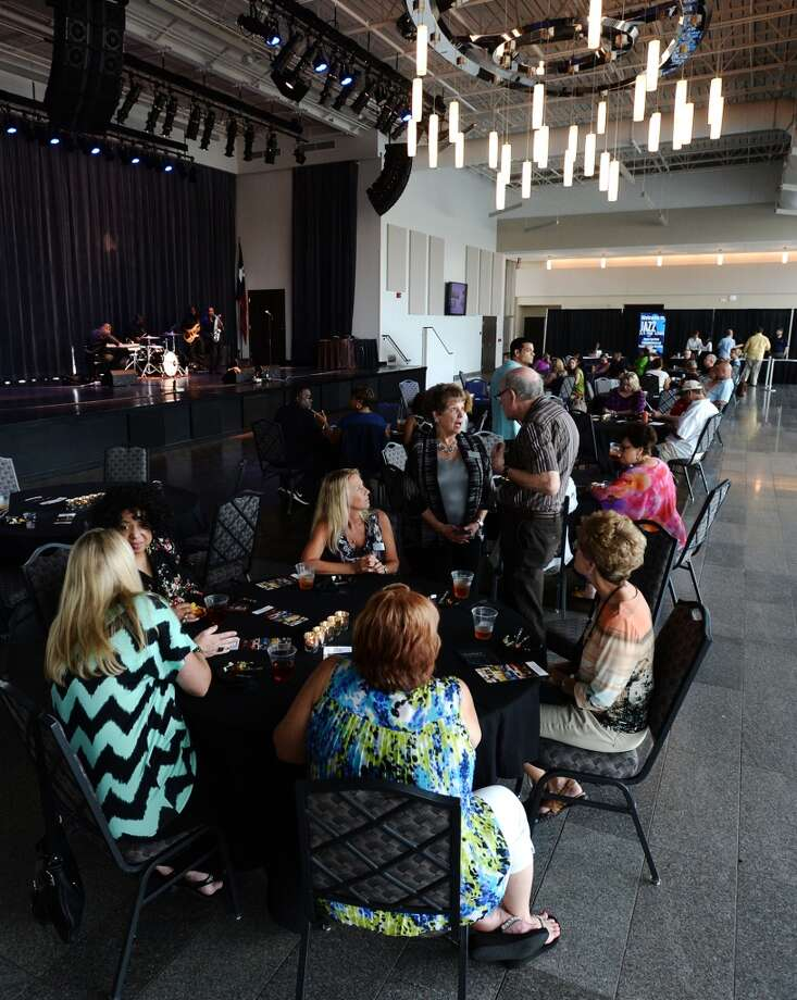 People mingle while Dean James and his band play at the Event Centre during Thursday's concert. The Jazz at the Lake concert series kicked off at the Event Centre Thursday night with Dean James and his band. There was also free food, beer tastings, and a cash bar for attendees of the free event. Photo taken Tuesday 7/29/14 Jake Daniels/@JakeD_in_SETX