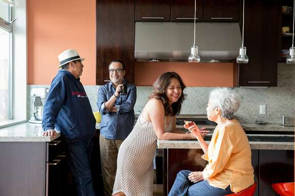 The multigenerational solution: Alex (left) Juan Carlos, Lizzette and Blanca Henriquez gather in the kitchen of their Excelsior district home.