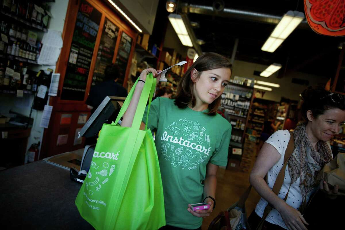 An Instacart personal shopper, Sydney Hollings-worth, carries a customer's order after purchasing it last month at a San Francisco grocery store.