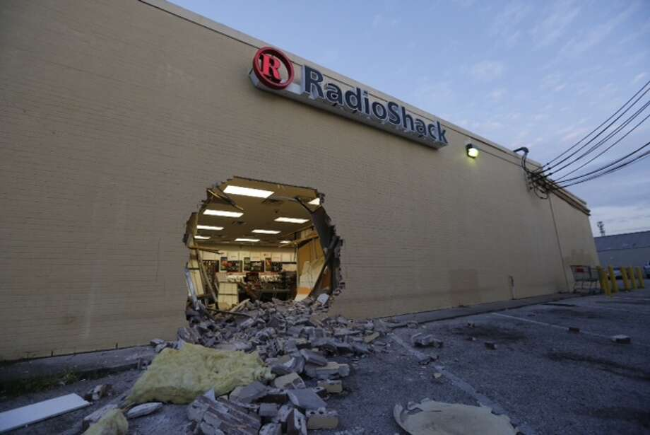 Houston police say smash-and-grab thieves left their van behind after ramming a hole through the wall of a Radio Shack and running away. Photo: Cody Duty / Houston Chronicle
