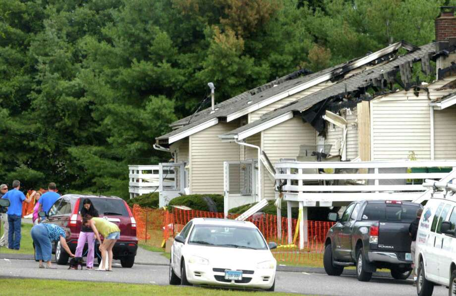 Family and friends gather at the Candlewood condominiums along Route 7 South in New Milford about 24 hours after a fire had destroyed several units and rendered their occupants temporarily without their homes. Aug. 22, 2014 Photo: Norm Cummings / The News-Times
