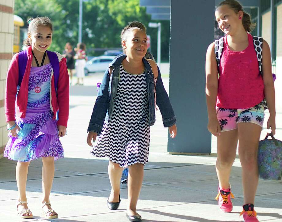 Upbeat and eager to go as they arrive at Sarah Noble Intermediate School for the first day of school in New Milford are, from left to right, Alexis Wright, 9, Averie Hatfield, 8, and Ariana Taylor, 9. Aug. 25, 2014 Photo: Trish Haldin / The News-Times Freelance