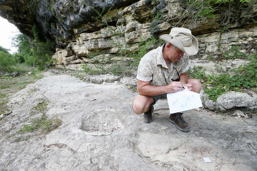 Dr. Thomas Adams assigns track numbers to white tiles marking sauropod tracks on the lower trackway during the third day of work with the dinosaur tracks at Government Canyon State Natural Area on Thursday, Aug. 7, 2014.  MARVIN PFEIFFER/ mpfeiffer@express-news.net Photo: MARVIN PFEIFFER, Marvin Pfeiffer/ Express-News / Express-News 2014
