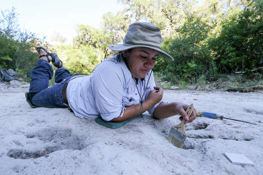 Diana Azouggagh, a student at UTSA, carefully cleans out a dinosaur track on the upper trackway during the sixth day of work at Government Canyon State Natural Area on Thursday, Aug. 14, 2014.  MARVIN PFEIFFER/ mpfeiffer@express-news.net Photo: MARVIN PFEIFFER, Marvin Pfeiffer/ Express-News / Express-News 2014