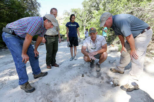 Russell Fishbeck, Deptuty Director of Texas Parks and Wildlife Department, (from left), Chris Holm, Superindentent of Government Canyon State Natural Area, Jennifer Shaffer, Dr Thomas Adams and Todd McClanahan, Region Director of Texas Parks and Wildlife, inspect dinosaur tracks on the upper trackway at Government Canyon State Natural Area on Thursday, Aug. 14, 2014.  MARVIN PFEIFFER/ mpfeiffer@express-news.net Photo: MARVIN PFEIFFER, Marvin Pfeiffer/ Express-News / Express-News 2014