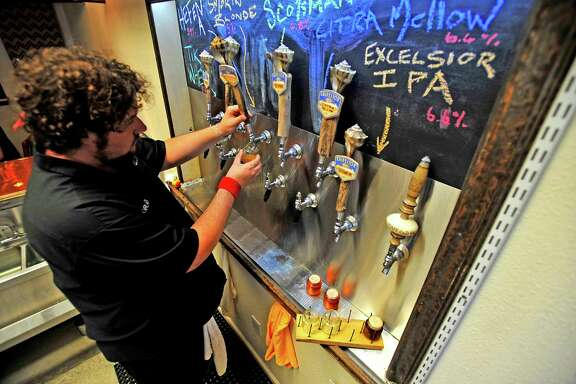 Graeme Bell pours a flight of six beers on tap at Galveston Island Brewing.