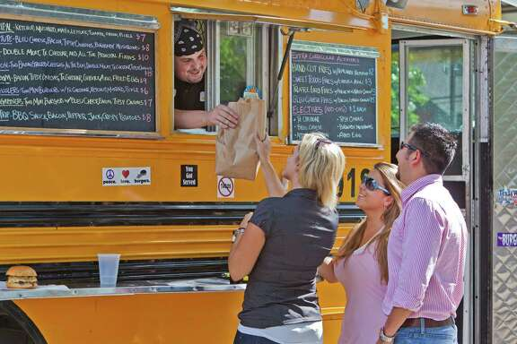 Food shoot on Bernie's Burger Bus, located at 2715 Sackett Street today in the parking lot of Lizzard's Pub. ID: Justin Turner hands a bag of goodies to Crystal Winters (blonde); Amanda Lindau (in pink) and Eliseo Acevedo (guy in sunglasses). Friday 6/03/11 (Craig H. Hartley/For the Chronicle)