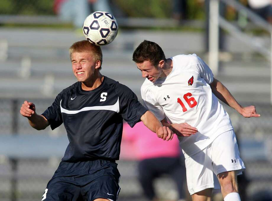 Staples soccer player Michael Reid goes up for a header despite the defensive efforts of the Cardinals Kelian Dequeker in an FCIAC match in Greenwich on Saturday. Greenwich won the game, 4-1. © J. Gregory Raymond for The Greenwich Time Photo: J. Gregory Raymond / Stamford Advocate Freelance;  © J. Gregory Raymond