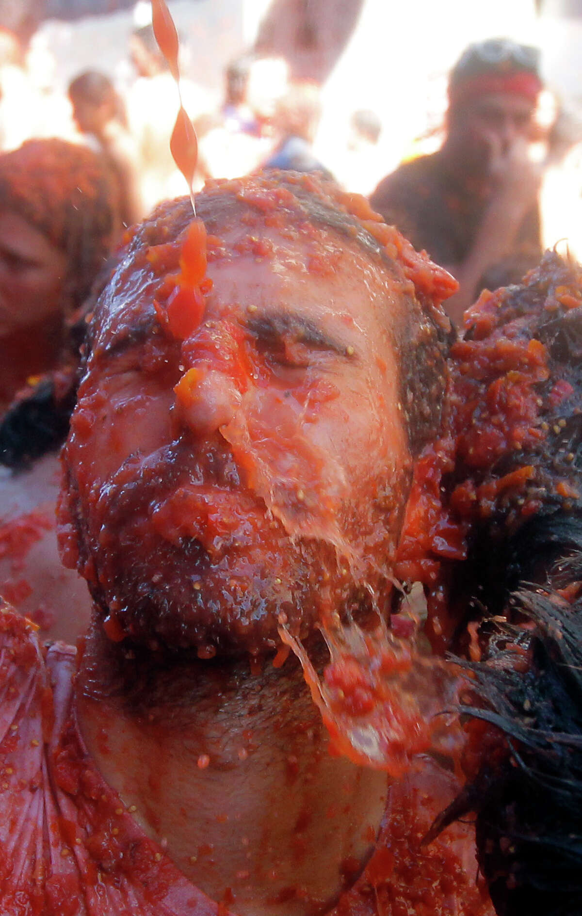 A man reacts as he is hit with tomatoes, during the annual
