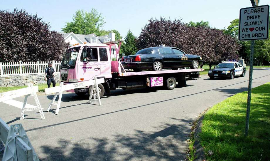 The Stamford Taxi in which the driver was killed in a stabbing on Doolittle Road in Stamford, Conn., is removed from the scene by a tow truck on Wednesday, August 27, 2014. Photo: Lindsay Perry / Stamford Advocate