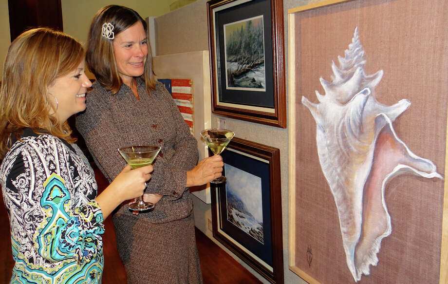 "At last year's Pequot Library Art Show, Catherine Cunningham and Kellie Panus examined a piece called ""Gift from the Sea."" The library has issued a call to artists in all mediums for entries in its 17th annual show, scheduled in mid-October. Photo: Mike Lauterborn / Fairfield Citizen contributed"