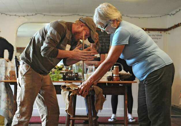 """Flying Deer nature center employee Josh Wood, left, demonstrates how to start a fire by rubbing a stick with the help from Noorunisa Smallen, Abode director, during a media preview for Behold! New Lebanon, a """"living museum of contemporary rural life"""" at the Abode Farm Thursday, Aug. 21, 2014, in New Lebanon, N.Y. (Lori Van Buren / Times Union) Photo: Lori Van Buren / 00028264A"""