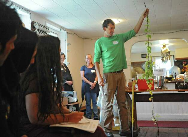"""Alex Olchowski of Spring Hill Hops holds a stalk of hops as he talks about growing the crop during a media preview for Behold! New Lebanon, a """"living museum of contemporary rural life"""" at the Abode Farm Thursday, Aug. 21, 2014, in New Lebanon, N.Y. (Lori Van Buren / Times Union) Photo: Lori Van Buren / 00028264A"""