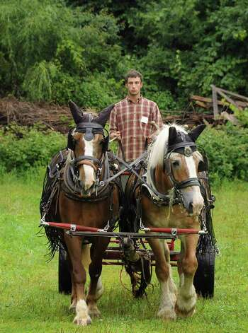 """Evan Thaler-Null, who runs Abode Farm CSA, takes a ride after demonstrating how to hitch the horses to a plow during a media preview for Behold! New Lebanon, a """"living museum of contemporary rural life"""" at the Abode Farm Thursday, Aug. 21, 2014, in New Lebanon, N.Y. (Lori Van Buren / Times Union) Photo: Lori Van Buren / 00028264A"""
