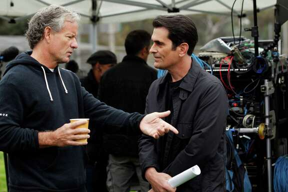 "Executive producer Christopher Lloyd works with star Ty Burrell on the set of ""Modern Family."""