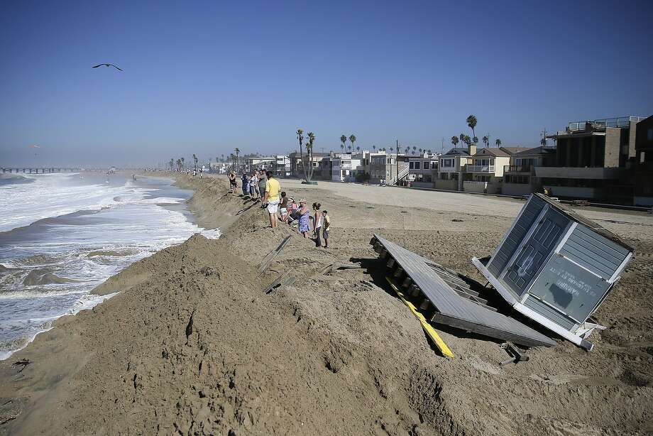 A lifeguard tower knocked over by high tides sits on the beach as people stand on the sand wall on Wednesday, Aug. 27, 2014, in Seal Beach, Calif. Parts of the low-lying Southern California coastal community of Seal Beach has been inundated by a surge of rising seawater brought on by Hurricane Marie spinning off Mexico's Pacific coast.  Photo: Jae C. Hong, Associated Press