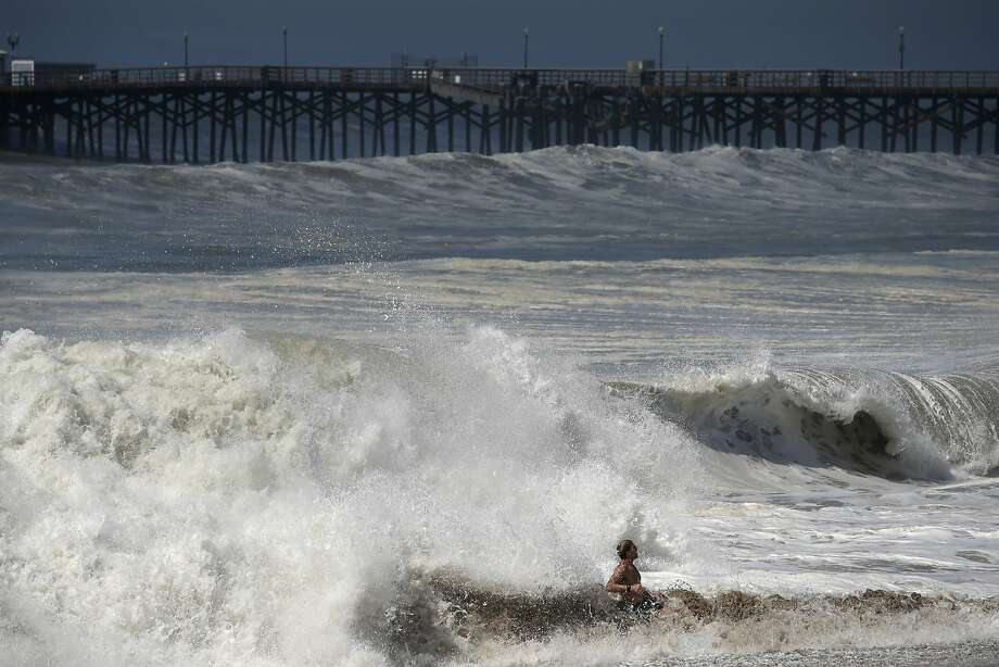 A man is hit by waves on Wednesday, Aug. 27, 2014, in Seal Beach, Calif. A low-lying street in the Southern California coastal community of Seal Beach has been inundated by a surge of rising seawater brought on by Hurricane Marie spinning off Mexico's Pacific coast. Photo: Jae C. Hong, Associated Press