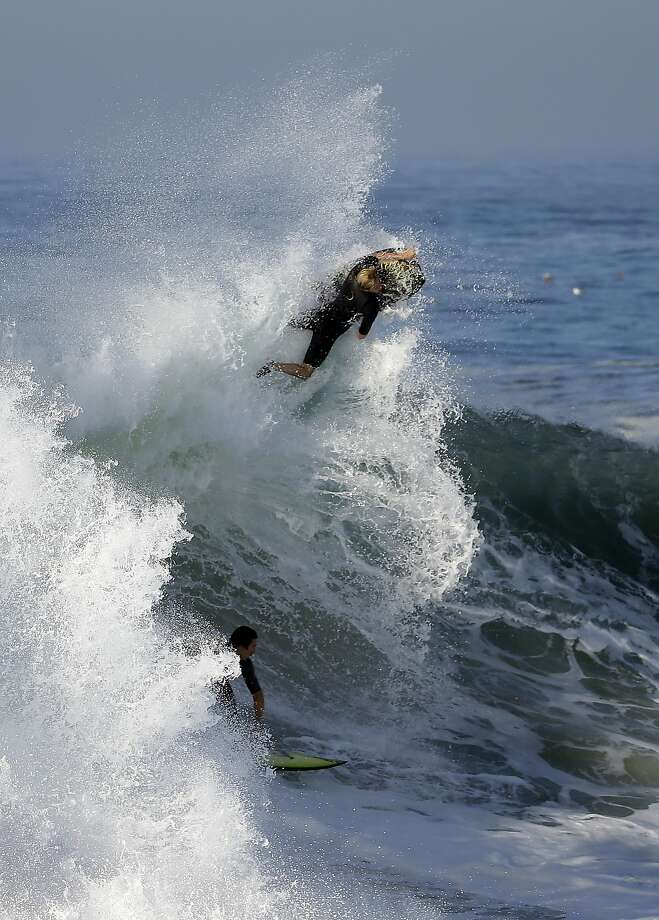 A bogie boarder and a surfer ride a wave at the wedge, on Wednesday, Aug. 27, 2014 in Newport Beach, Calif. Beach goers experienced much higher than normal surf, brought on by Hurricane Marie spinning off the coast on Mexico. Photo: Chris Carlson, Associated Press