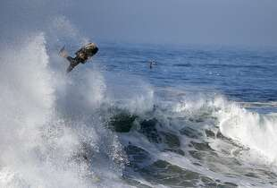 A boogieboarder flies over a wave a surfer rides underneatch a wave at the wedge in Newport Beach, Calif., Wednesday, Aug. 27, 2014. Southern California beachgoers experienced much higher than normal surf, brought on by Hurricane Marie spinning off the coast of Mexico. (AP Photo/Chris Carlson)