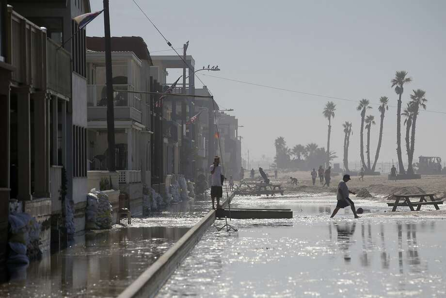 A man walks through the flooded beachfront properties on Wednesday, Aug. 27, 2014, in Seal Beach, Calif. A low-lying street in the Southern California coastal community of Seal Beach has been inundated by a surge of rising seawater brought on by Hurricane Marie spinning off Mexico's Pacific coast. Photo: Jae C. Hong, Associated Press