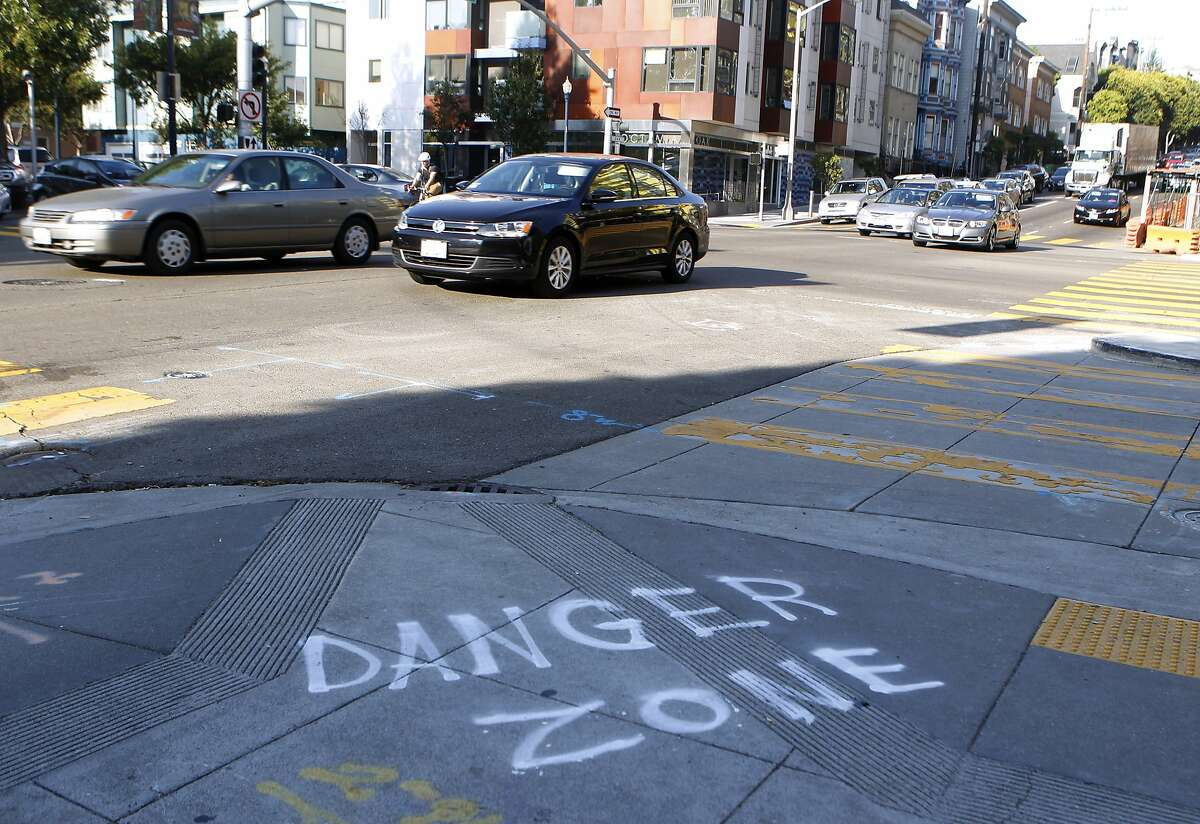 A message is sprayed on the sidewalk at the intersection of Oak Street and Octavia Boulevard in San Francisco, Calif. on Wednesday, Aug. 27, 2014. Some motorists turning on Oak onto Octavia cut into the right turn lane at the last minute - or make an illegal right turn from the left lanes - creating large backups and irking other drivers.