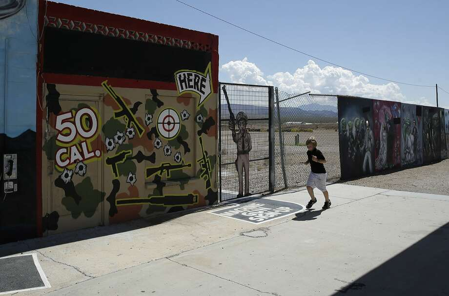 A child runs by the Last Stop outdoor shooting range in White Hills, Ariz., two days after an instructor was accidentally killed by a 9-year-old with an Uzi. Photo: John Locher, Associated Press