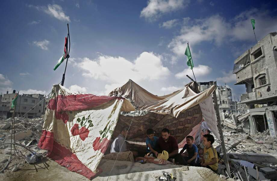 Palestinians rest in an improvised shelter made with blankets stretched between wooden poles on the rubble of their destroyed house in Gaza City. Photo: Khalil Hamra, Associated Press