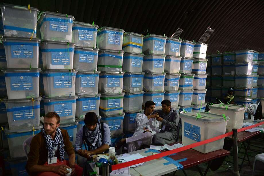 "Afghan election commission workers wait to begin the audit of the presidential run-off vote in the country's general election at a counting centre in Kabul on August 27, 2014.  Afghanistan's fraud-hit election teetered on the brink of collapse August 27 as one of the two candidates boycotted the UN-supervised vote audit set up to end a prolonged dispute over the rightful winner.   Abdullah Abdullah, who claims that massive fraud was committed against him in the June 14 vote, pulled out of the audit after his senior campaign officials dismissed the process for invalidating fake votes as ""a joke"".  AFP PHOTO/SHAH MaraiSHAH MARAI/AFP/Getty Images Photo: Shah Marai, AFP/Getty Images"