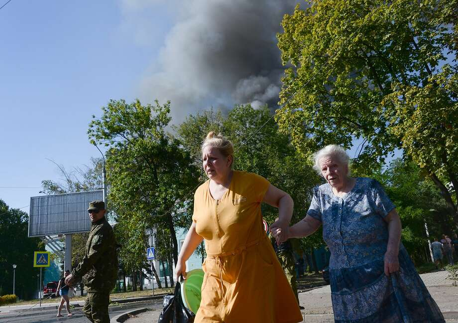 Women rush across the street after shelling  in the town of Donetsk, eastern Ukraine. Photo: Mstislav Chernov, Associated Press
