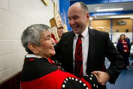 ADVANCE FOR USE SUNDAY, JAN. 29, 2012 AND THEREAFTER - In this Tuesday Jan. 10, 2012 photo, Haisla First Nation Chief Councillor Ellis Ross, right, laughs with Hereditary Chief Marilynn Furlan after he addressed the panel during the opening day of hearings for the Enbridge Northern Gateway Project in Kitamaat Village, British Columbia, Canada. Several hundred people gathered for hearings on whether a pipeline should be laid from the Alberta oil sands to the Pacific in order to deliver oil to Asia, chiefly energy-hungry China. The stakes are particularly high for the village of Kitamaat and its neighbors, because the pipeline would terminate here and a port would be built to handle 220 tankers a year and 525,000 barrels of oil a day. Ross used to work on whale-watching boats, and testified that the tanker port would go up just as marine life decimated by industrial pollution was making a comeback in his territory. (AP Photo/The Canadian Press, Darryl Dyck)