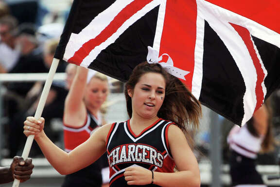 A Churchill cheerleader carries the Union Jack after a touchdown against MacArthur during high school football action at Comalander Stadium on Saturday, Oct. 6, 2012.