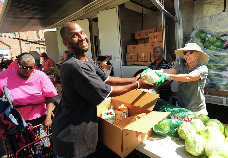 "Jesse Austin, who also calls himself ""God's poet"", of Bridgeport, receives a cabbage from volunteer Jill Gordon, of Westport, during the visit of the Connecticut Food Bank's mobile food pantry to the Victory Outreach  Church parking lot on Jane Street in Bridgeport, Conn. on Wednesday, August 27, 2014. The mobile pantry visits the site on the fourth Wednesday of every month at 10:30 a.m., and currently provides food to over two hundred households. Photo: Brian A. Pounds / Connecticut Post"