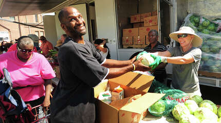 "Jesse Austin, who also calls himself ""God's poet"", of Bridgeport, receives a cabbage from volunteer Jill Gordon, of Westport, during the visit of the Connecticut Food Bank's mobile food pantry to the Victory Outreach  Church parking lot on Jane Street in Bridgeport, Conn. on Wednesday, August 27, 2014. The mobile pantry visits the site on the fourth Wednesday of every month at 10:30 a.m., and currently provides food to over two hundred households."