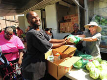 """Jesse Austin, who also calls himself """"God's poet"""", of Bridgeport, receives a cabbage from volunteer Jill Gordon, of Westport, during the visit of the Connecticut Food Bank's mobile food pantry to the Victory Outreach  Church parking lot on Jane Street in Bridgeport, Conn. on Wednesday, August 27, 2014. The mobile pantry visits the site on the fourth Wednesday of every month at 10:30 a.m., and currently provides food to over two hundred households."""